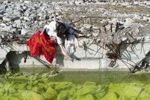 Dancer Eiko Otate sits on a wall next to a still body of water.