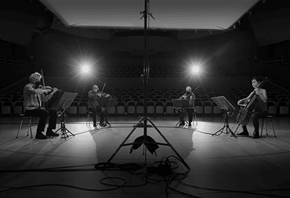 black-and-white photo of Kronos Quartet performing on stage